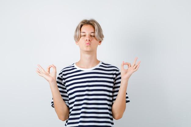 Portrait d'un jeune garçon adolescent montrant un signe de mudra, gardant les yeux fermés, faisant la moue des lèvres en t-shirt rayé et ayant l'air détendue vue de face