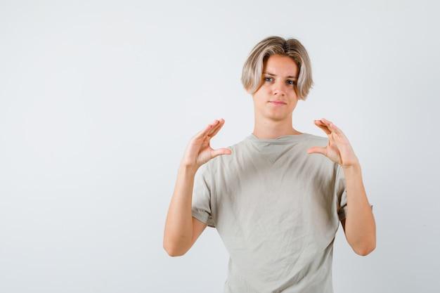 Portrait de jeune garçon adolescent montrant un signe de taille en t-shirt et à la vue de face sensible