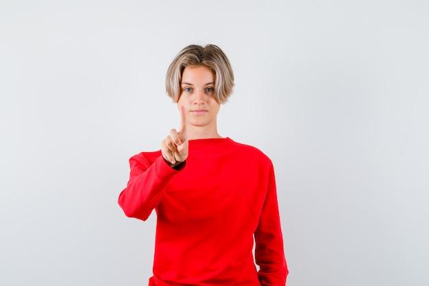 Portrait de jeune garçon adolescent montrant tenir un geste minute en pull rouge et à la vue de face confiant