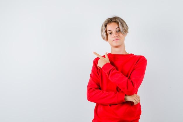 Portrait de jeune garçon adolescent pointant vers le coin supérieur gauche en pull rouge et à la vue de face confiant
