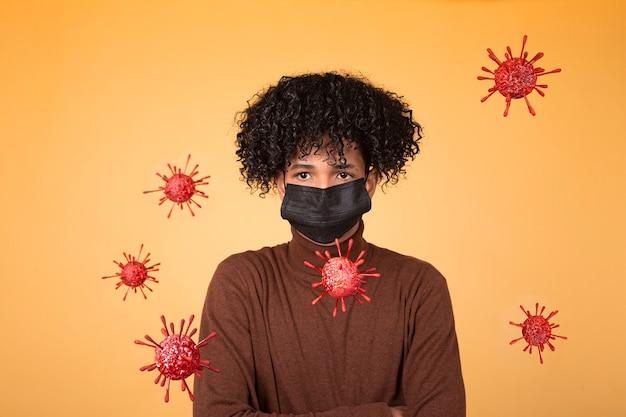 Portrait de jeune garçon afro cheveux avec masque médical sur fond jaune avec des molécules de bactéries. épidémie, virus, santé. copier l'espace