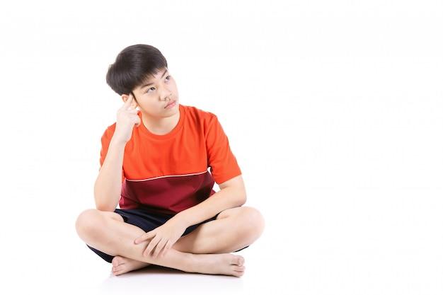 Portrait de jeune garçon asiatique assis sur fond blanc,