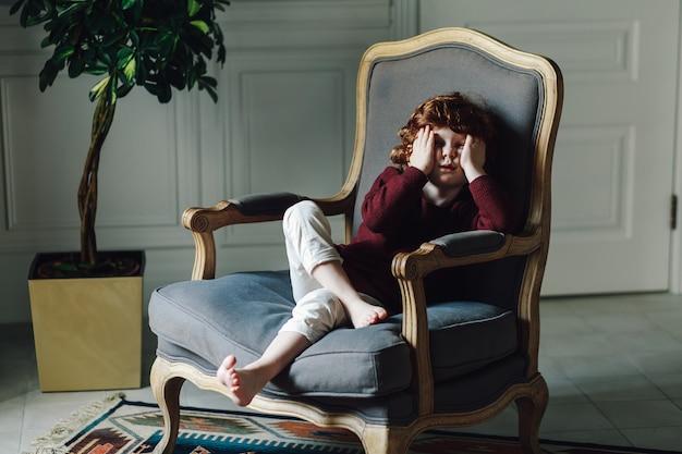 Portrait d'un jeune garçon assis dans le fauteuil et s'appuyant sur sa main