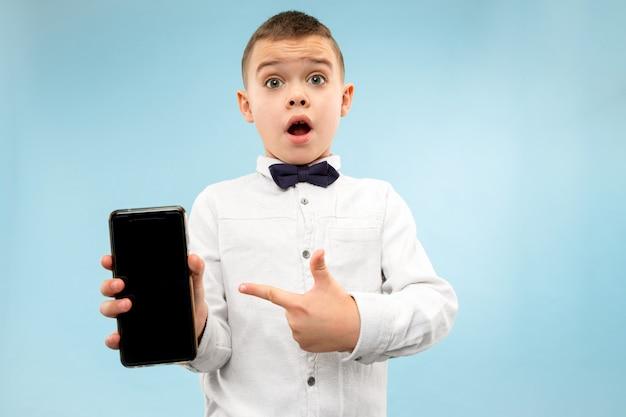 Portrait de jeune garçon attrayant tenant un smartphone vierge