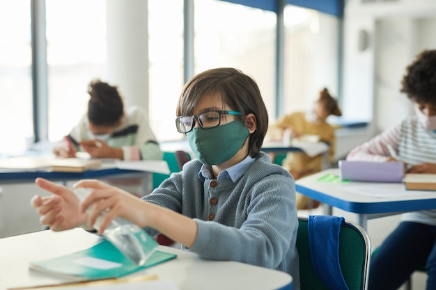 Portrait de jeune garçon désinfectant les mains dans la salle de classe, mesures de sécurité covid, espace de copie