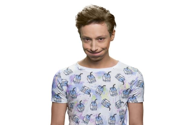 Portrait de jeune garçon européen tirant un visage. garçon adolescent drôle isolé sur mur blanc.