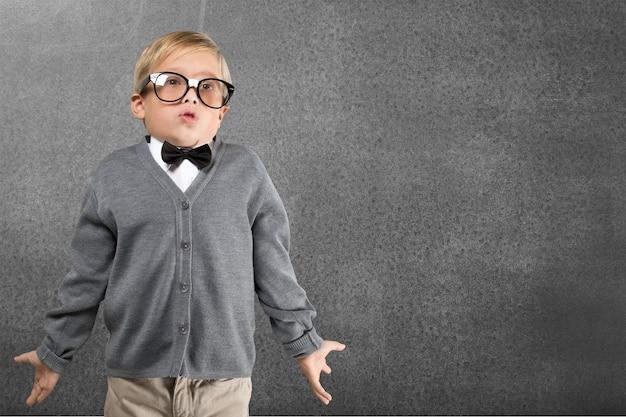 Portrait d'un jeune garçon mignon dans des verres en pensant à l'arrière-plan