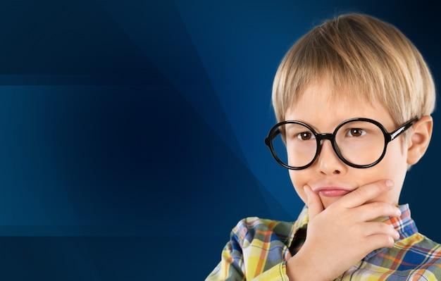 Portrait d'un jeune garçon mignon avec des lunettes isolé sur fond. prise de vue en studio.