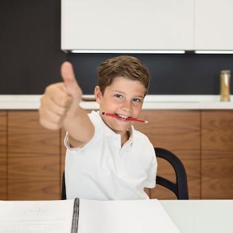 Portrait de jeune garçon montrant les pouces vers le haut