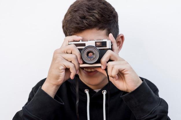 Portrait de jeune garçon prenant la photo à travers la caméra rétro sur fond blanc
