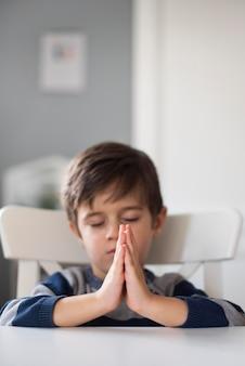 Portrait de jeune garçon priant à la maison