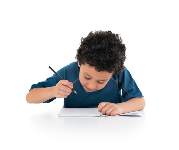 Portrait de jeune garçon qui étudie et fait sur fond blanc