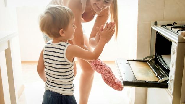 Portrait d'un jeune garçon souriant de 3 ans avec une jeune mère qui prépare des biscuits savoureux et sucrés au four dans la cuisine. cuisine familiale ensemble à la maison