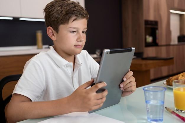 Portrait de jeune garçon tenant une tablette
