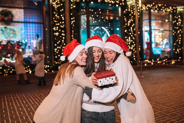 Portrait d'un jeune groupe d'amis heureux et mignon qui s'embrassent et sourient en marchant à la veille de noël à l'extérieur, portant des chapeaux de père noël, de nombreuses lumières sur le