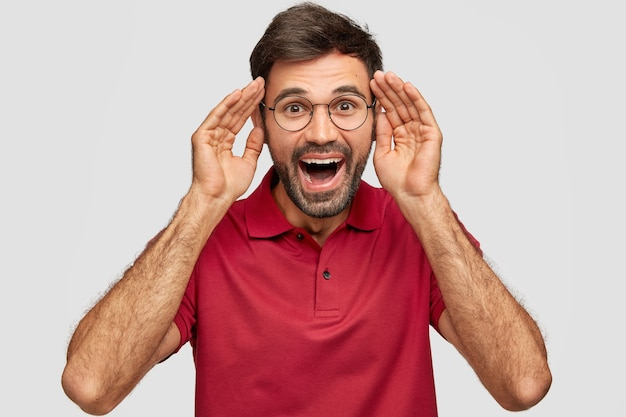 Portrait de jeune hipster mâle barbu ravi garde les mains près de la tête, a une expression joyeuse, s'amuse avec des amis, ouvre largement la bouche, rit positivement, isolé sur un mur blanc