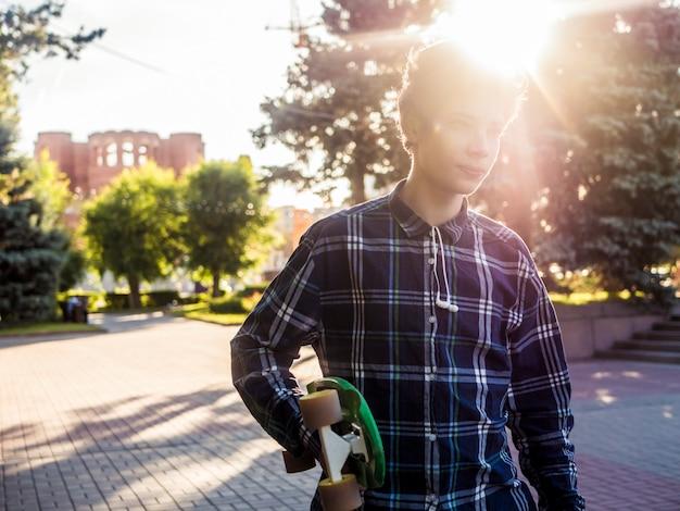 Portrait de jeune hipster portant penny board dans la ville contre le soleil