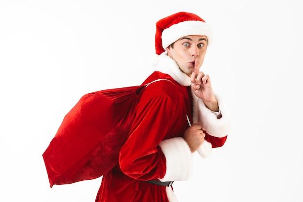 Portrait de jeune homme 30 s en costume de père noël et chapeau rouge marchant avec sac-cadeau sur l'épaule