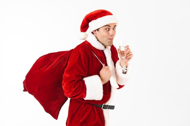 Portrait de jeune homme 30 s en costume de père noël et chapeau rouge tenant un sac-cadeau et boire du champagne