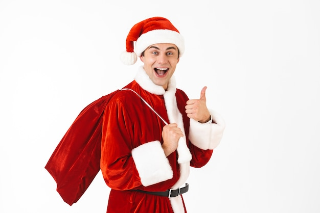 Portrait de jeune homme 30 s en costume de père noël et chapeau rouge transportant un sac-cadeau sur l'épaule