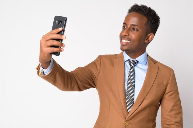 Portrait de jeune homme d'affaires africain aux cheveux afro en costume marron contre le mur blanc