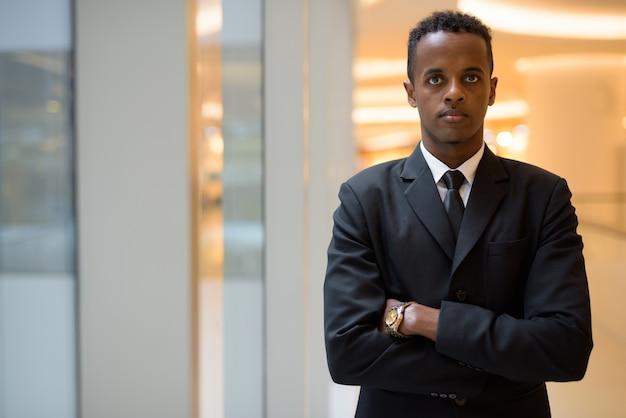Portrait de jeune homme d'affaires africain avec les bras croisés