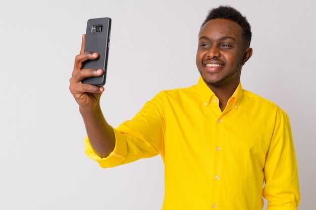 Portrait de jeune homme d'affaires africain avec chemise jaune contre le mur blanc