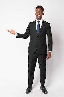 Portrait de jeune homme d'affaires africain avec des cheveux afro en costume contre un mur blanc