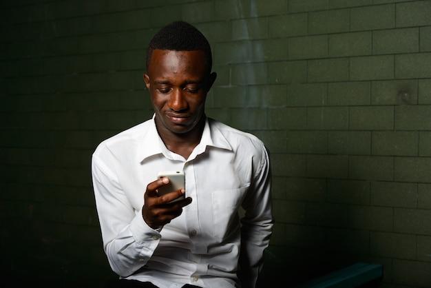 Portrait de jeune homme d'affaires africain dans l'obscurité contre le mur de briques dans la nuit