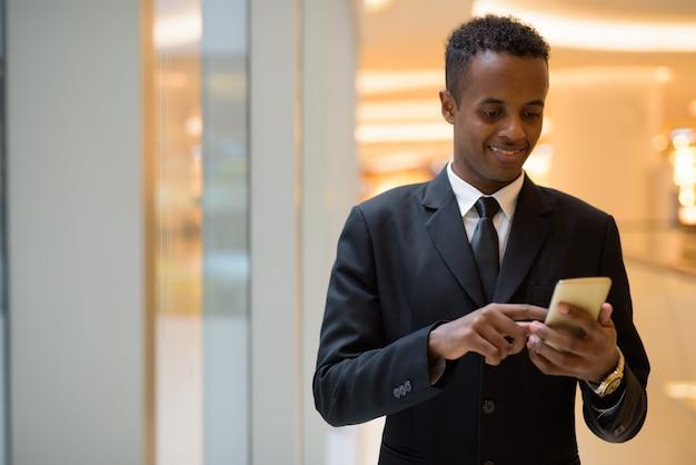 Portrait de jeune homme d'affaires africain heureux à l'aide de téléphone mobile
