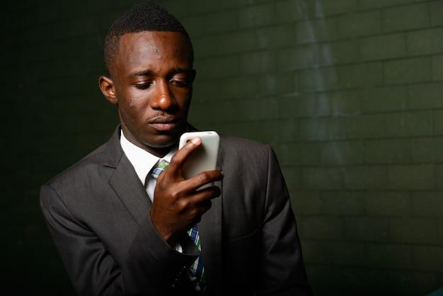 Portrait de jeune homme d'affaires africain portant un costume contre le mur de briques dans l'obscurité