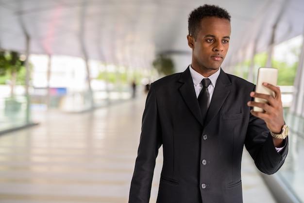 Portrait de jeune homme d'affaires africain prospère à l'aide de téléphone mobile à l'extérieur