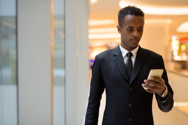 Portrait de jeune homme d'affaires africain utilisant un téléphone mobile