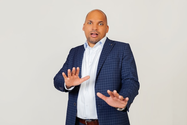 Portrait de jeune homme d'affaires afro-américain choqué, effrayé et effrayé par l'expression de la peur, a arrêté le geste de la main, criant sous le choc. concept de panique.