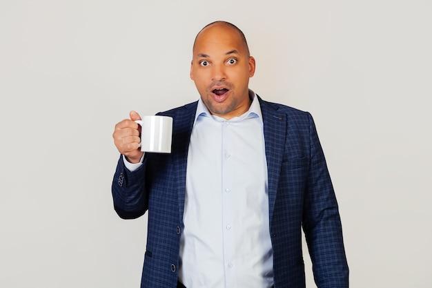 Portrait d'un jeune homme d'affaires afro-américain étonné, buvant une tasse de café, effrayé choqué par le visage surpris, effrayé et excité par l'expression de la peur.
