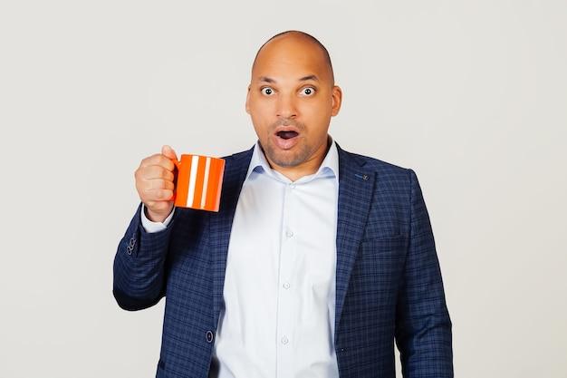 Portrait d'un jeune homme d'affaires afro-américain étonné, tenant une tasse de café dans sa main, effrayé choqué par un visage surpris, effrayé et excité par une expression de peur.