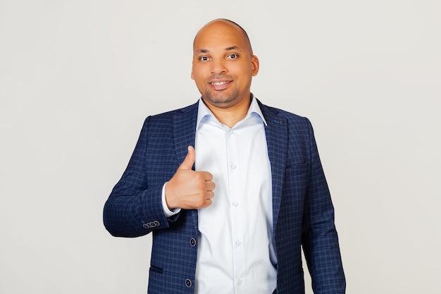 Portrait d'un jeune homme d'affaires afro-américain prospère faisant un geste de la main heureuse. confirmation de l'expression du visage montrant le succès tout en regardant.