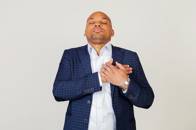 Portrait de jeune homme d'affaires afro-américain reconnaissant souriant avec les mains sur la poitrine avec les yeux fermés et le geste reconnaissant sur le visage. concept de santé.
