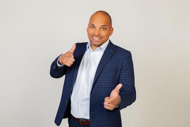 Portrait d'un jeune homme d'affaires afro-américain réussi, pointant ses doigts avec un visage heureux et drôle. bonne énergie et bonne ambiance.