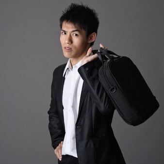 Portrait de jeune homme d'affaires asiatique beau avec mallette