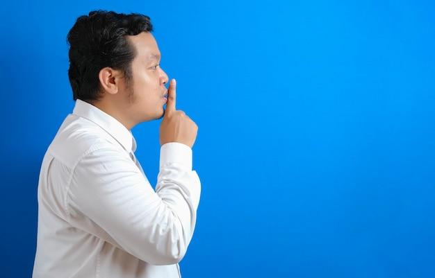 Portrait de jeune homme d'affaires asiatique demandant à être silencieux, geste de silence, concept de silence