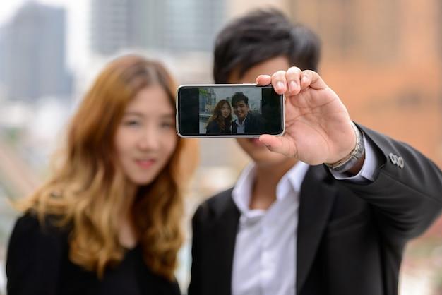 Portrait de jeune homme d'affaires asiatique et jeune femme d'affaires asiatique ensemble dans la ville en plein air