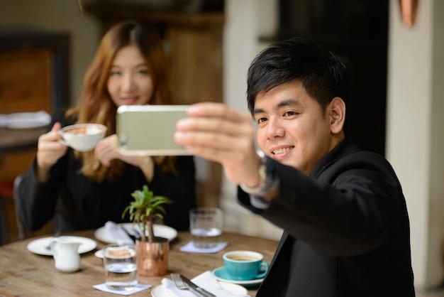 Portrait de jeune homme d'affaires asiatique et jeune femme d'affaires asiatique ensemble se détendre au café