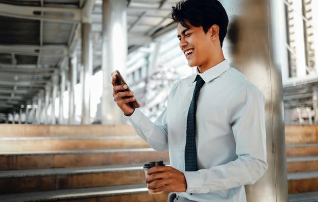 Portrait d'un jeune homme d'affaires asiatique souriant à l'aide de téléphone portable dans la ville