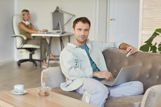 Portrait de jeune homme d'affaires assis sur un canapé et travaillant sur un ordinateur portable en ligne à l'aide d'une carte de crédit pour le paiement avec son collègue en arrière-plan