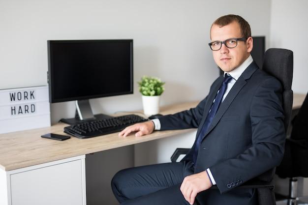 Portrait de jeune homme d'affaires beau assis dans un bureau moderne