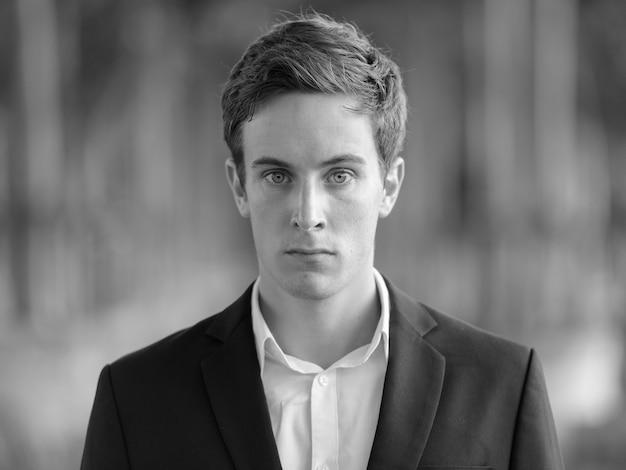 Portrait de jeune homme d'affaires beau en costume à l'aéroport à l'extérieur en noir et blanc