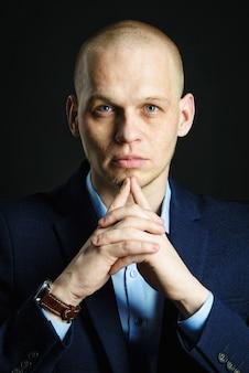 Portrait de jeune homme d'affaires beau en costume sombre avec les mains jointes