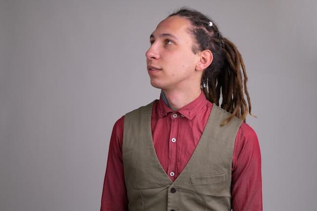 Portrait de jeune homme d'affaires beau avec des dreadlocks contre un mur blanc