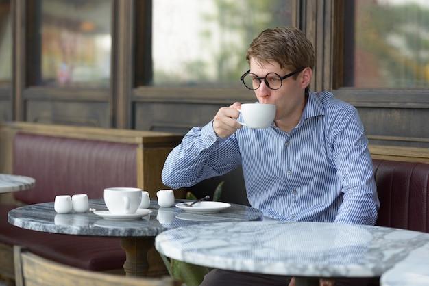Portrait de jeune homme d'affaires blond beau se détendre au café en plein air